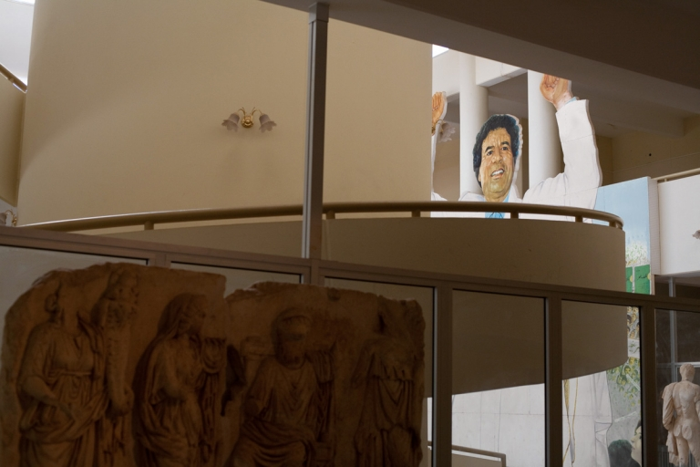 Poster of Libyan dictator Gaddafi peers over ancient scupltures in Leptis Magna museum in Libya