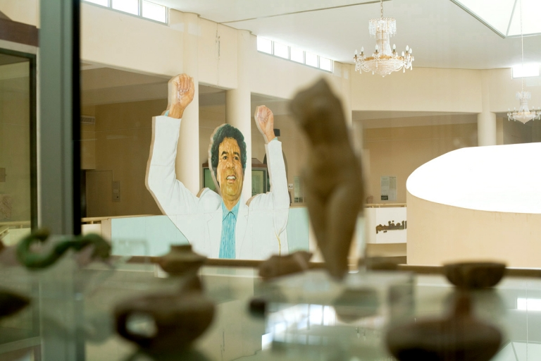 Libyan dictator Gaddafi peers over ancient scupltures in Leptis Magna museum in Libya