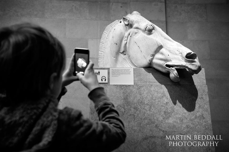 Boy using an ipod to photograph a sculpture from The Parthenon at The British Museum