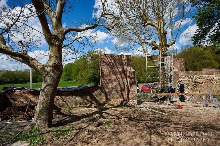Workmen work on the restored North Gate at Hougoumont